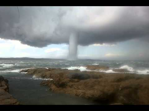 A waterspout is an intense columnar vortex that occurs over a body of water. They most commonly appear as funnel-shaped clouds connected to a cumuliform or cumulonimbus cloud. Only the strongest versions that spawn from mesocyclones (like land-based t ...
