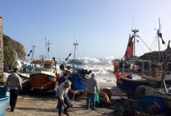 fishermen pulling their boats up to safety at Cadgwith