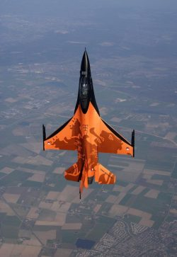 A Dutch F-16 Falcon above a typical Dutch landscape
