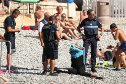 Disgusting to see this in 2016, 4 armed police forcing a woman to remove a Burqini, WTF France?! ...