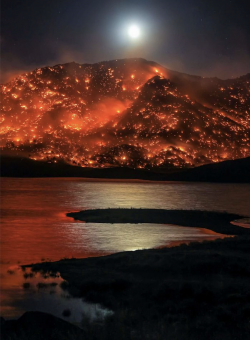 Moon rising over burning California hills, in Lake Isabella