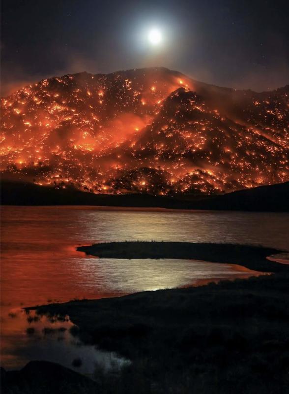 Moon rising over burning California hills, in Lake Isabella