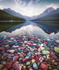 The rocks in the Bowman Lake in Montana are caused by the presence of Iron which gives the rocks ...