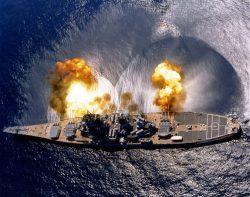 The USS Iowa firing a full broadside of nine 16″ shells